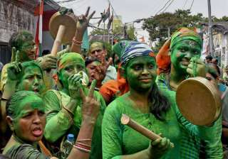 Smeared in green and armed with musical instruments, Trinamool Congress supporters celebrate their party's win in state assembly election in Kolkata on Thursday.