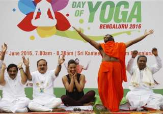 Bollywood actress Bipasha Basu, third left, laughs as yoga guru Sri Vachananand Swamiji, second right, performs yoga at an event to celebrate International Yoga Day in Bangalore.