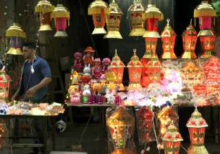 A Palestinian vendor stands between lighted traditional Ramadan lanterns while waiting for customers at the main market in Gaza City.
