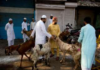 Indian Muslims buy goats for sacrifice after Eid al-Adha prayers at Jama Masjid in New Delhi.