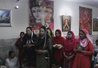 Women from the Hindu community worship during a ceremony to celebrate Diwali, at Krishna temple in Lahore, Pakistan.