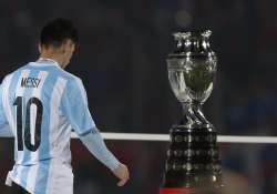Lionel Messi walking past the Copa America Trophy.