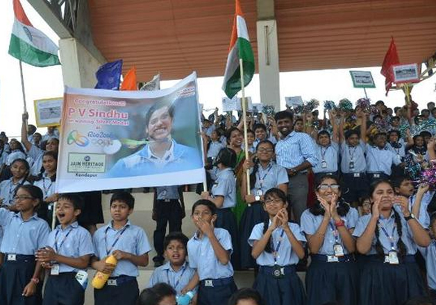 School children cheer for P.V. Sindhu during the felicitation ceremony at Gachibowli stadium in Hyderabad on Monday.
