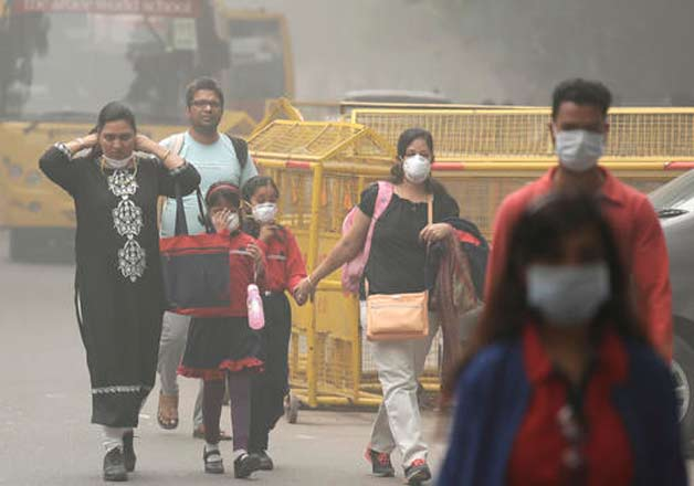 An Indian family arrives at a protest against air pollution in New Delhi, India, Sunday, Nov. 6, 2016. The Delhi government has ordered that all city schools be shut, construction activity halted and all roads be doused with water as crippling air pollution has engulfed the Indian capital.