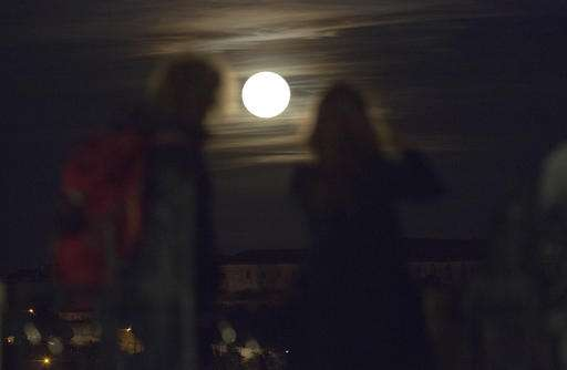 Two women took pictures of the full moon as it rose above Lisbon.