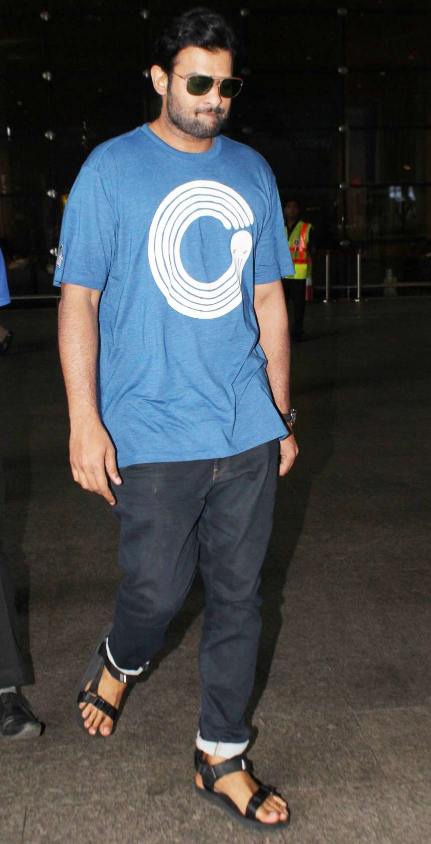 Prabhas: Bahubali star Prabhas was seen in a casual look wearing a basic graphic tee and blue denim along with black kittos at an airport.