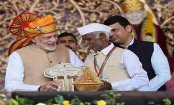 Prime Minister Narendra Modi hands over key of a house to a