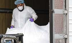 A body wrapped in plastic is loaded onto a refrigerated container truck used as a temporary morgue b