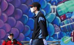 A pedestrian wears a face mask as he walks past a mural of a fish while strolling on the boardwalk a
