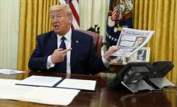 President Donald Trump holds up a copy of the New York Post as speaks before signing an executive or