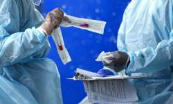 In this July 23, 2020 file photo, health care workers prepare a COVID-19 test sample before a person
