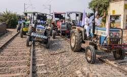 Farmers raise slogans as they block train tracks with
