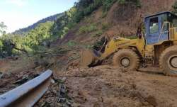 A bulldozer clears out the road damaged by landslide to access a village swamped by another landslid