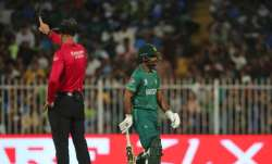 Pakistan's Fakhar Zaman walks off the field as the umpire